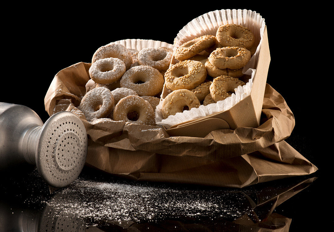 Cardboard boxes filled with round baked doughnuts in nuts and icing sugar on table