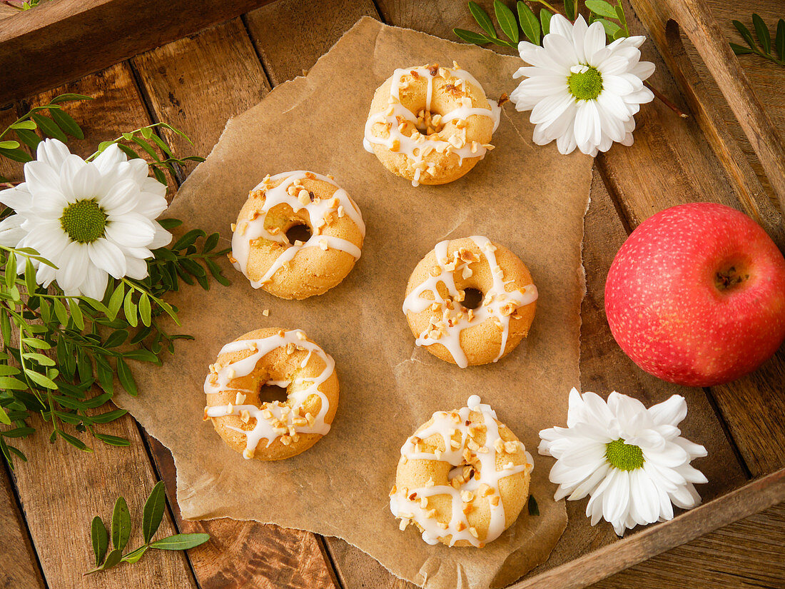 Apple doughnuts with icing and roasted hazelnuts