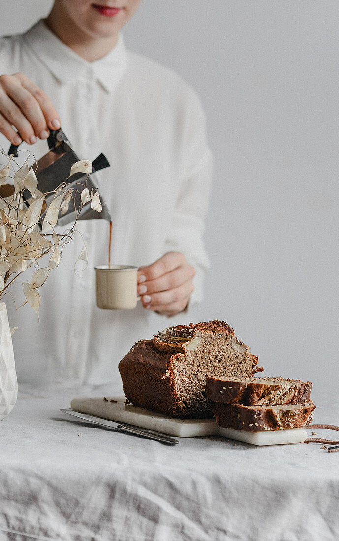 Woman pouring coffee, banana bread with sesame seeds