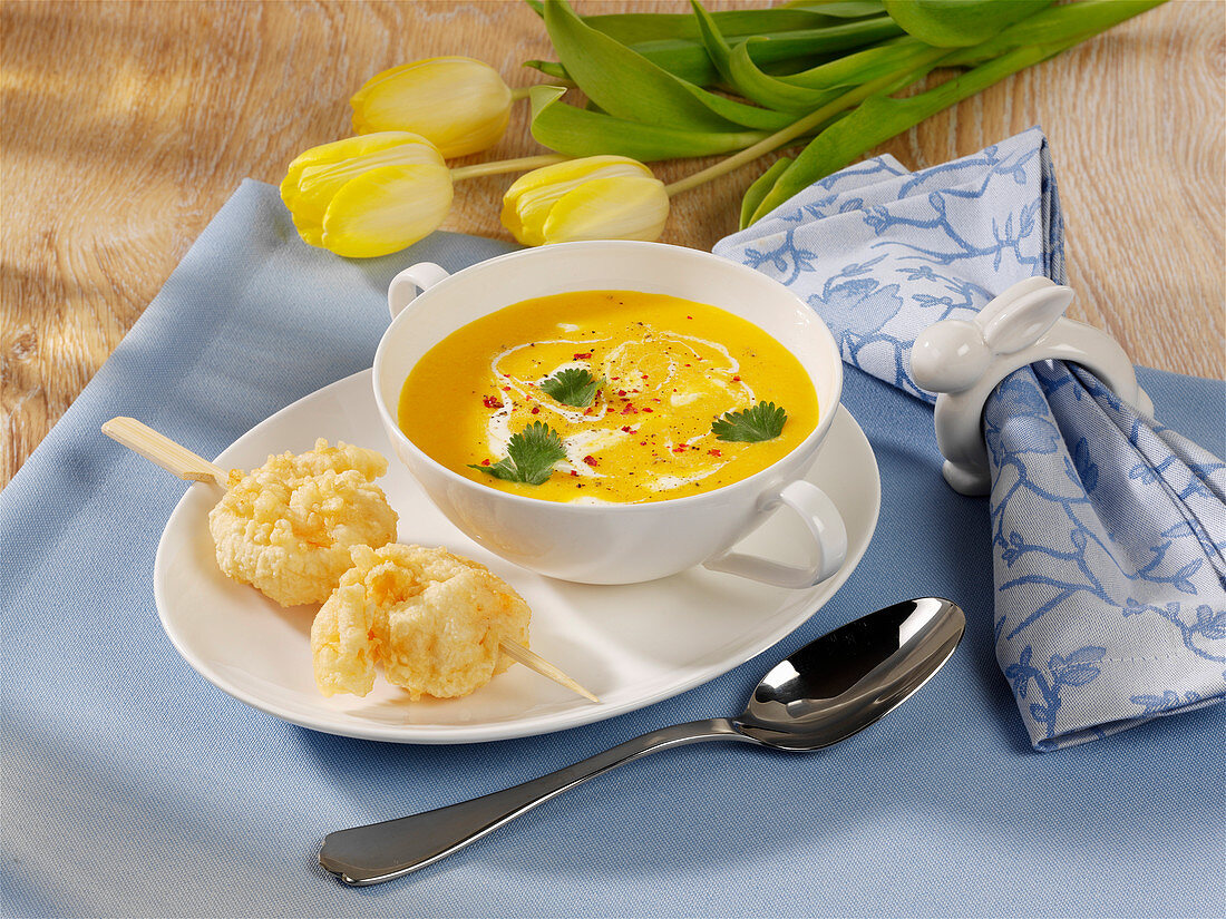 Carrot and mango soup with prawn skewers