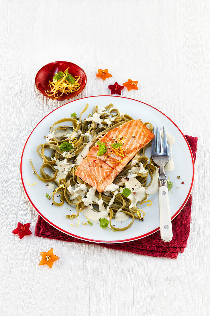 Salmon on green ribbon noodles with cheese sauce