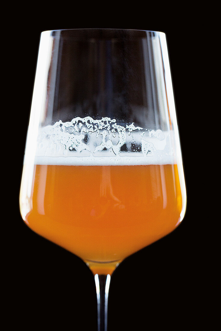 A glass of craft beer against a black background