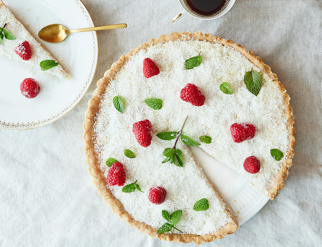 Cake with coconut sprinkles, raspberries and mint leaves