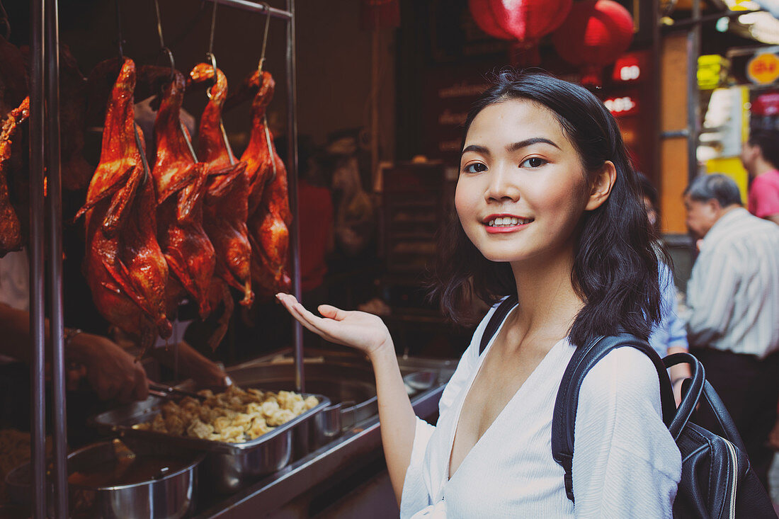 Young woman in Chinatown (Bangkok) with Peking ducks
