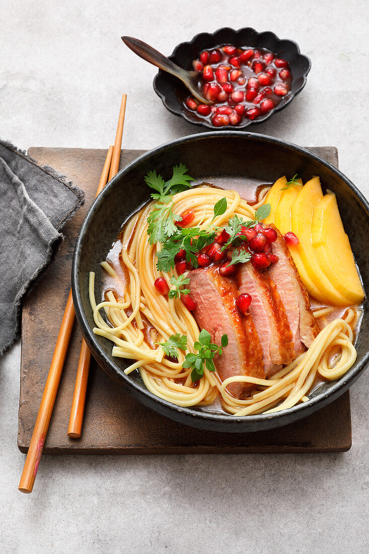 Asian noodle bowl with fried duck breast and mango