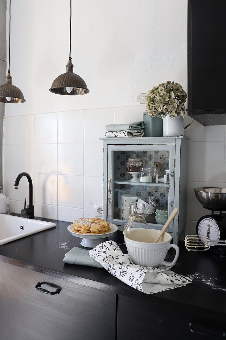 Baking utensils on worksurface in front of small glass-fronted cabinet