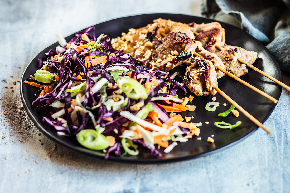 Satay with peanut sauce and red cabbage salad in Thai style