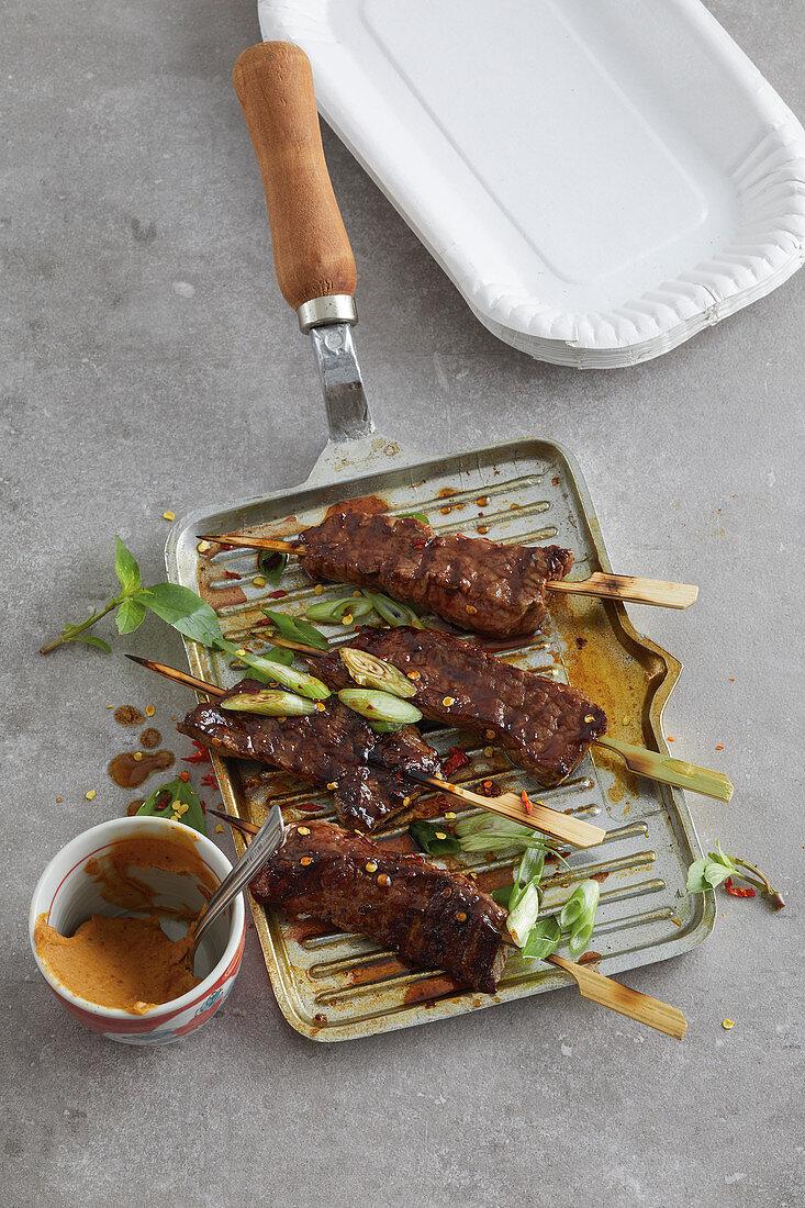 Spicy beef satay skewers with a peanut dip