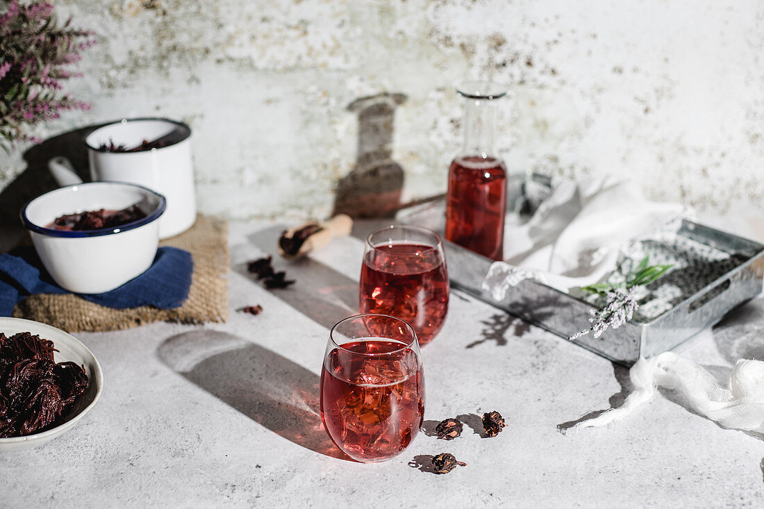 High angle of jar and glasses of delicious natural red hibiscus tea placed near pots with dry flowers on table against shabby wall