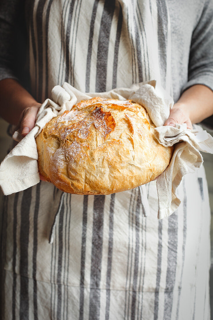 Woman wearing an apron holds freshly baked artisan bread in her hands