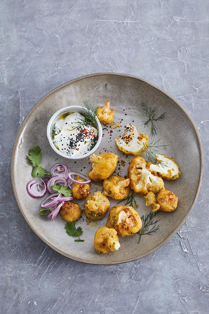 Baked cauliflower bahjis in a coriander coating with a dill and yoghurt dip