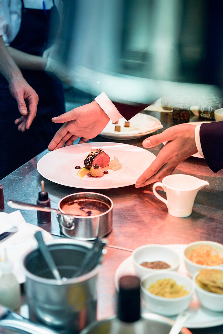 A waiter take a plate from the pass in a restaurant