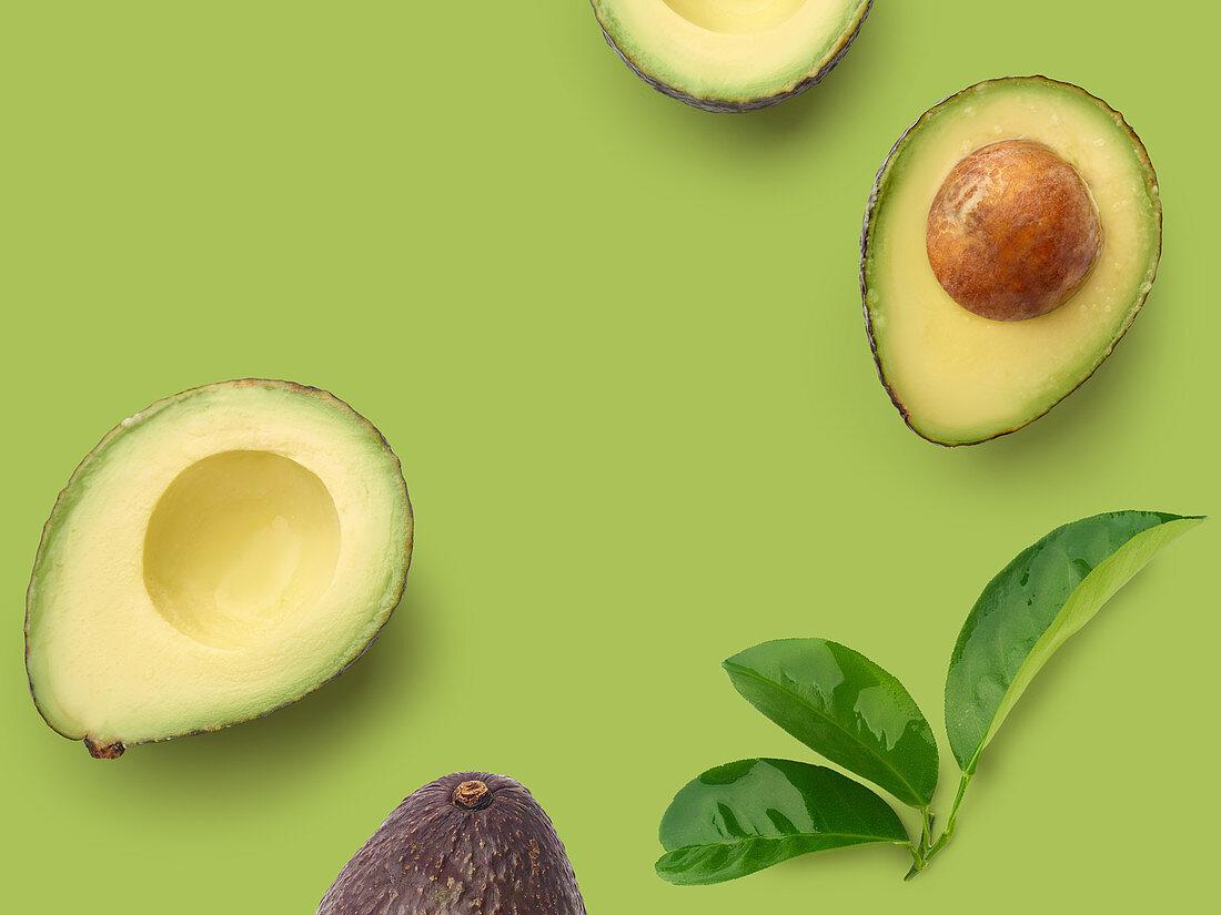 Halbierte Avocados auf grünem Untergrund