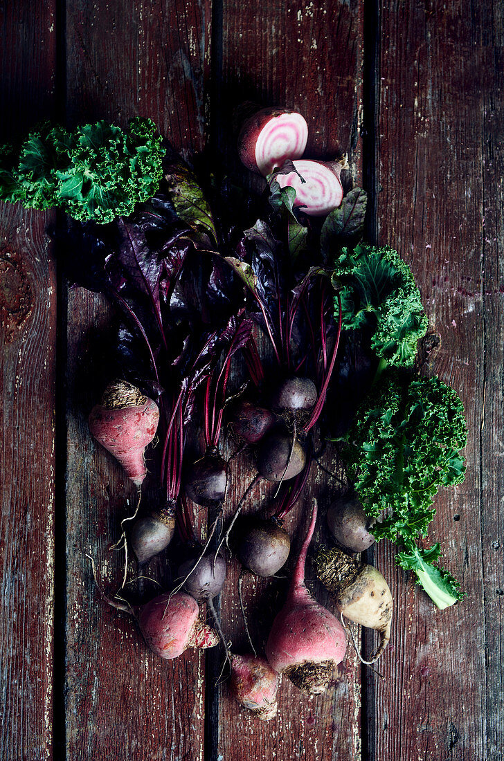Golden beets, chioggia beets and beetroots with kale on a wooden surface