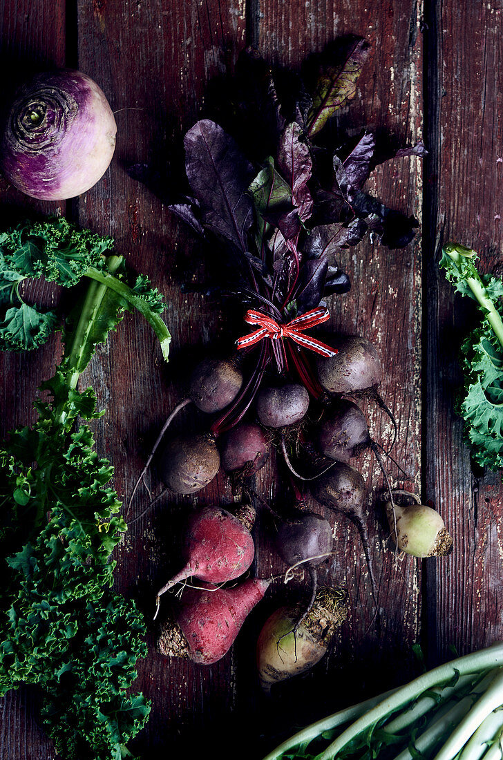 Golden beets, chioggia beets and beetroots with turnips and dandelions on a wooden surface