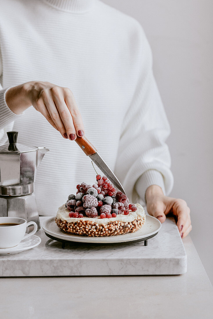 Vegan cake made of expanded millet and dates with cashew cream and fruit