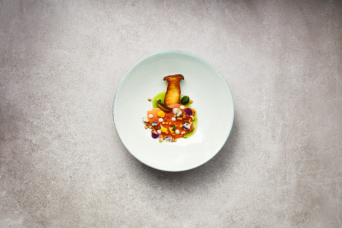 Fried king trumpet mushrooms with carrot leather and a parsley broth