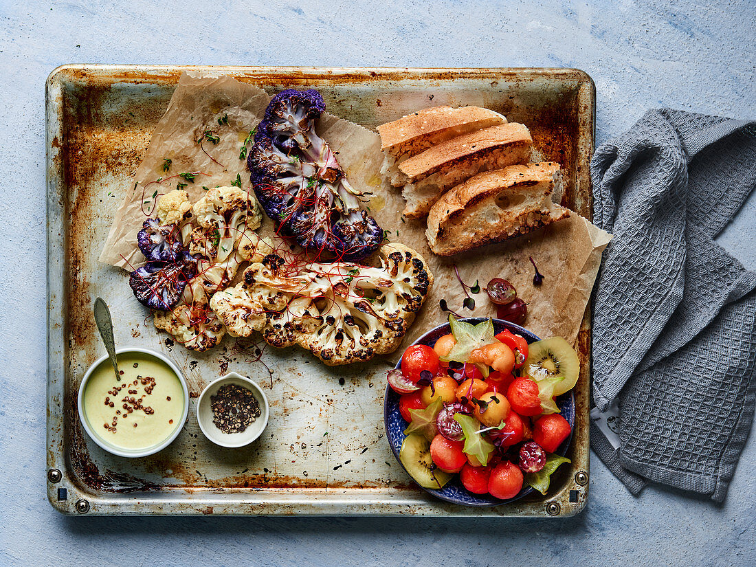 Roasted cauliflower on a baking tray with a melon salad, bread and a creamy dip