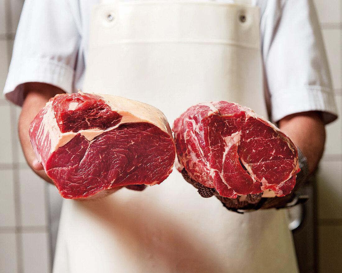 Butcher holds roast beef and entrecôte
