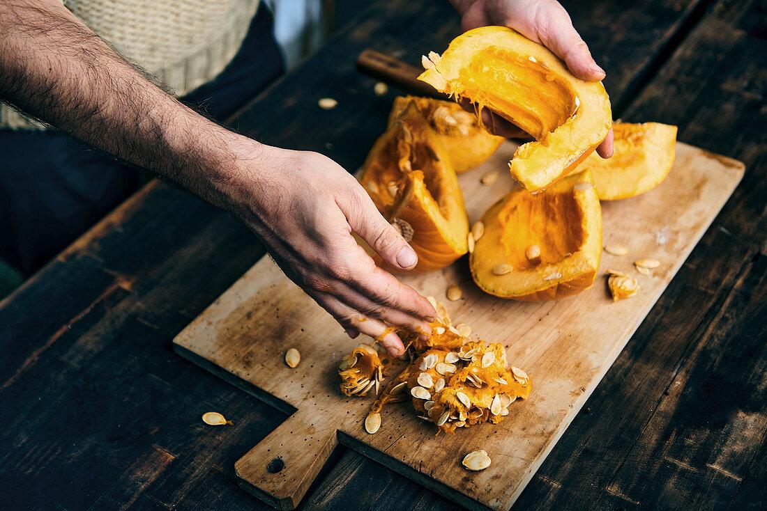 Hands cut pumpkin