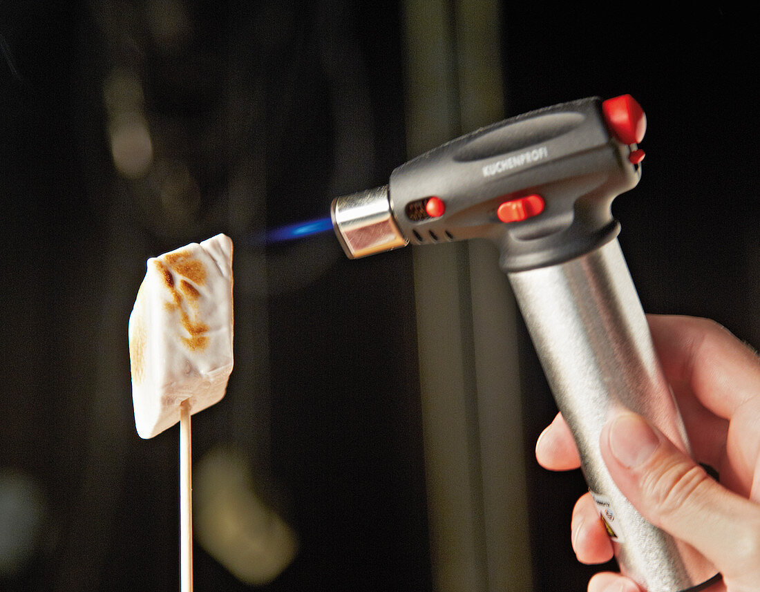 A marshmallow being toasted with a kitchen torch