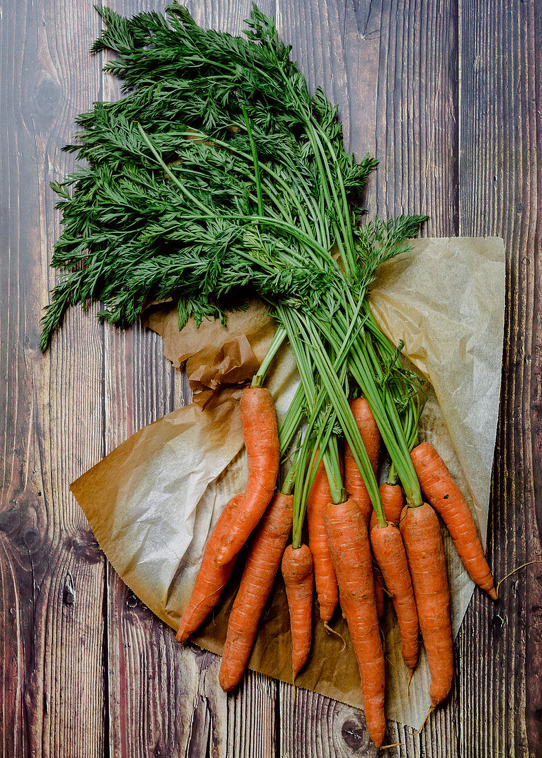 Fresh carrots with green leaves over wooden table