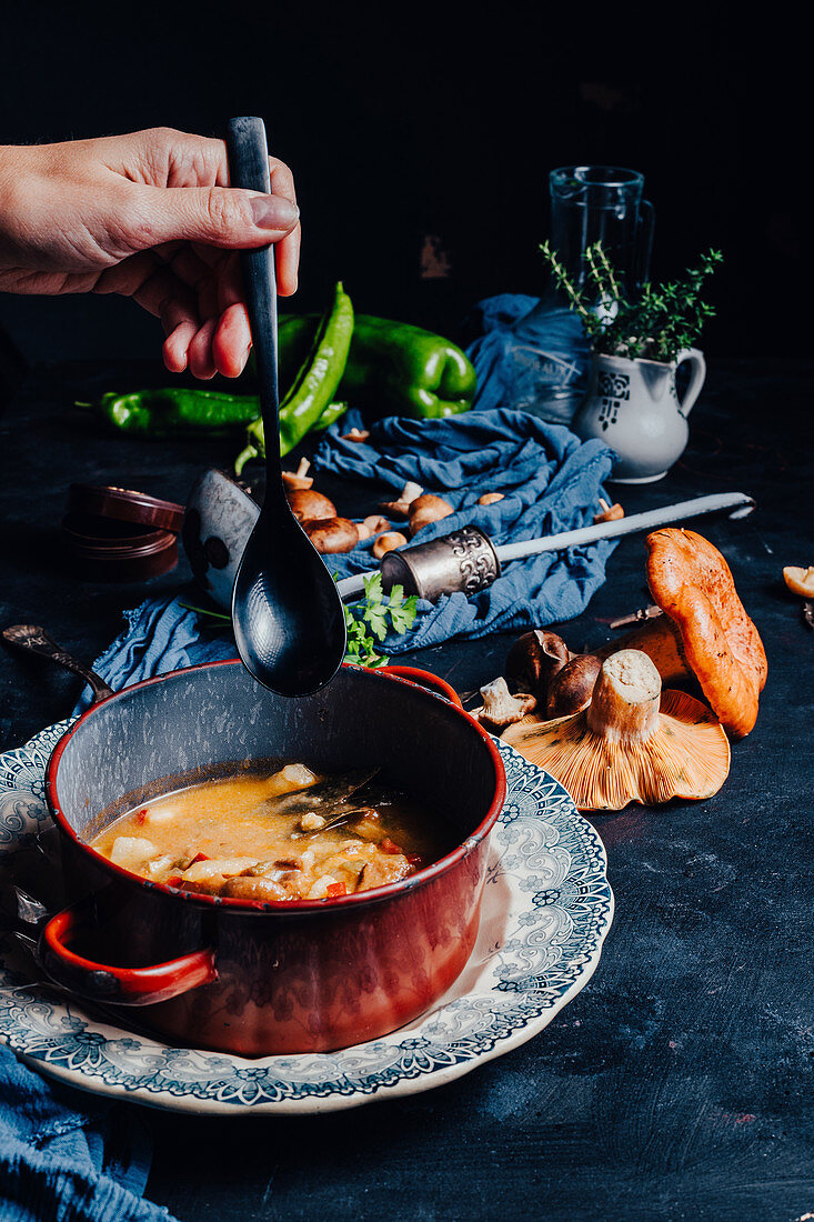 Hand holding a spoon near a bowl with delicious soup placed on table with red pine mushrooms and spicy green chili pepper