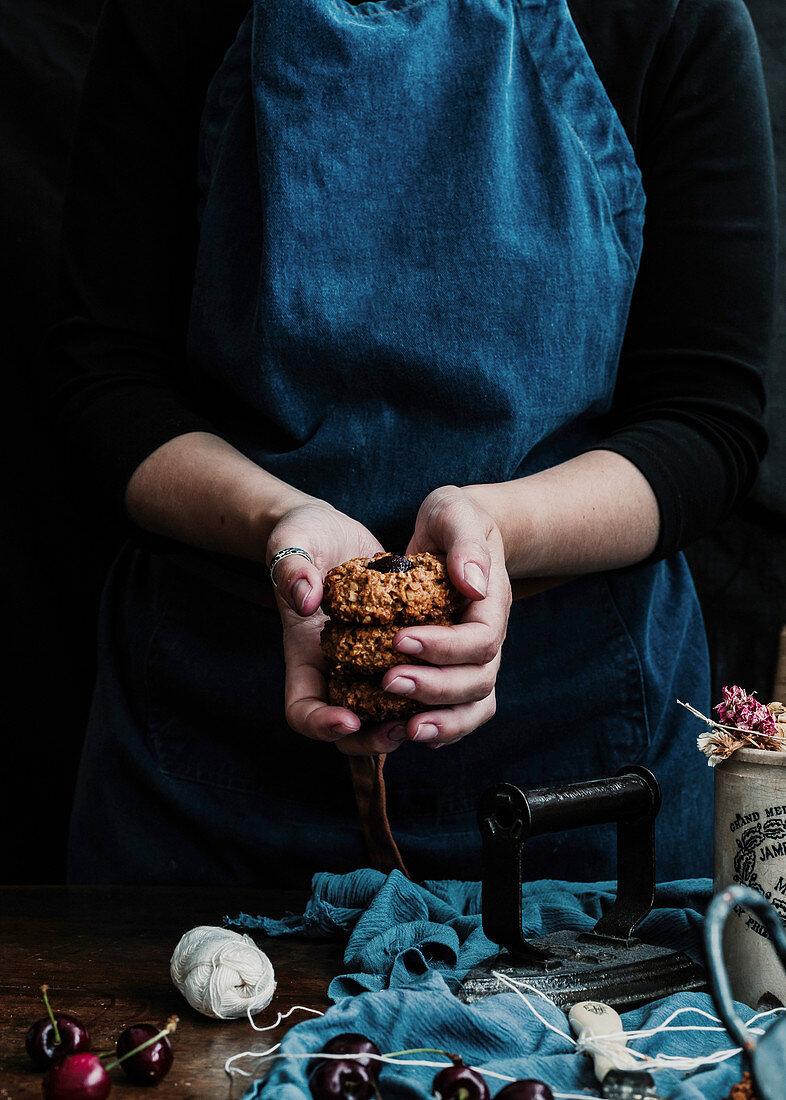 Hand with stack of cookies at table with fresh cherry and retro iron on cloth