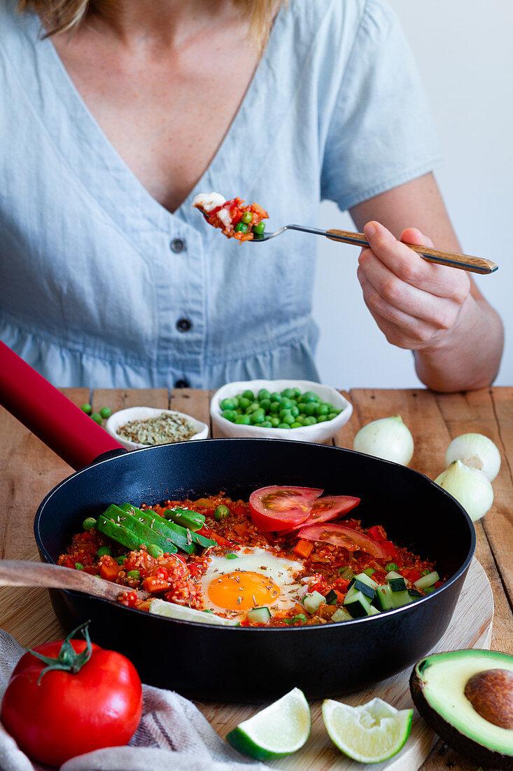 Frau isst Shakshuka mit Spiegelei und Quinoa