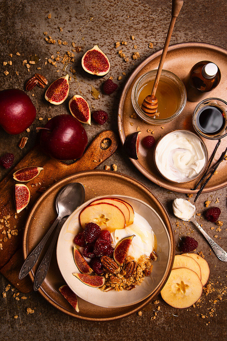 Bowl of vanilla yoghurt with granola, apples, figs, raspberries, honey and pecan nuts