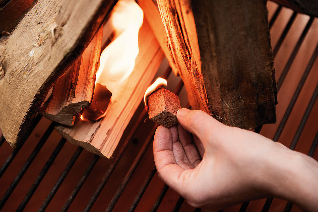 A burning fire starter being added to wood