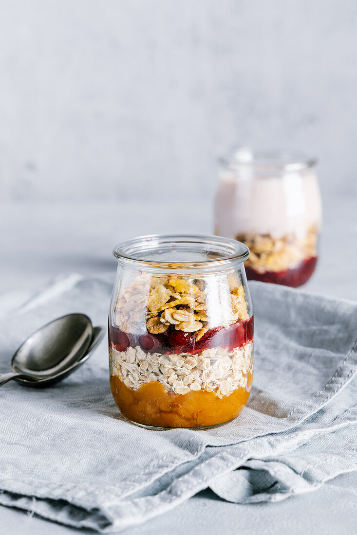 Cranberry and sea buckthorn sauce with granola in glass jar