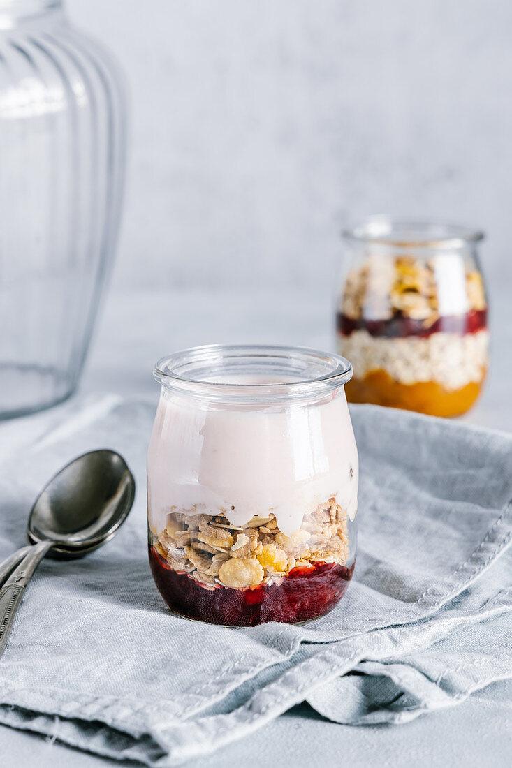 Healthy raspberry parfaits with yogurt in glass jars