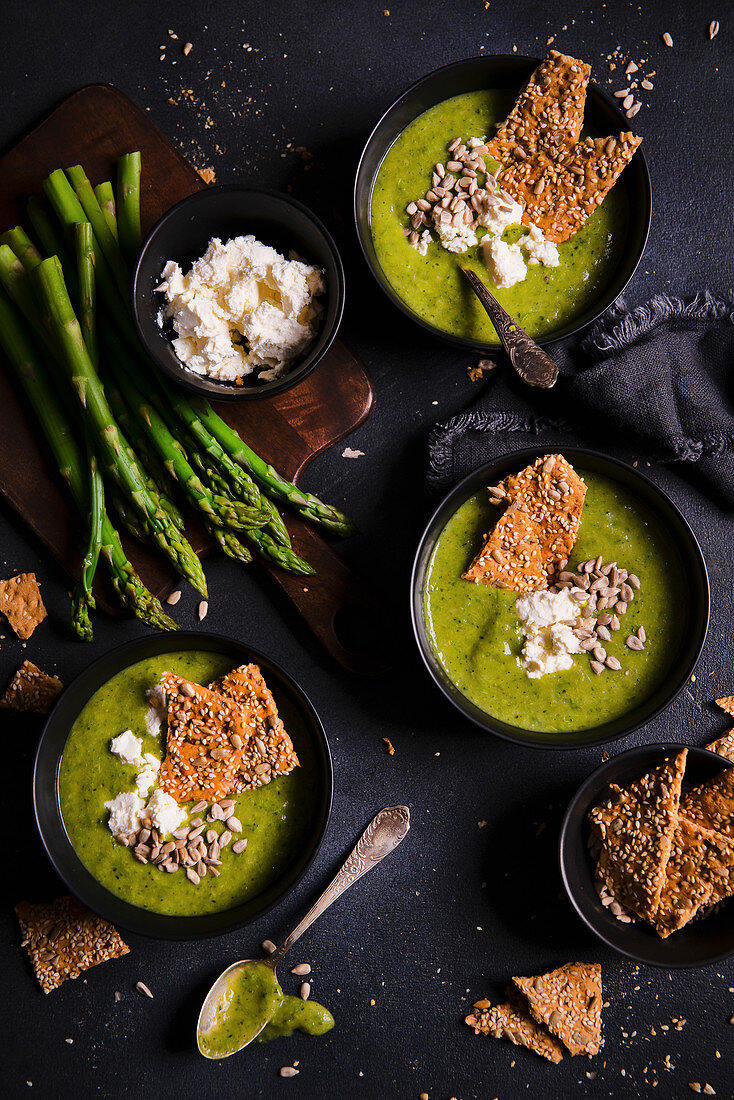 Green asparagus and broccoli cream soup with feta cheese, sunflower seeds and crispy bread