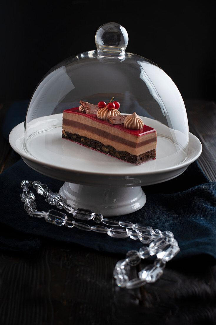 An elegant redfruit and chocolate patisserie in a glass cake dome