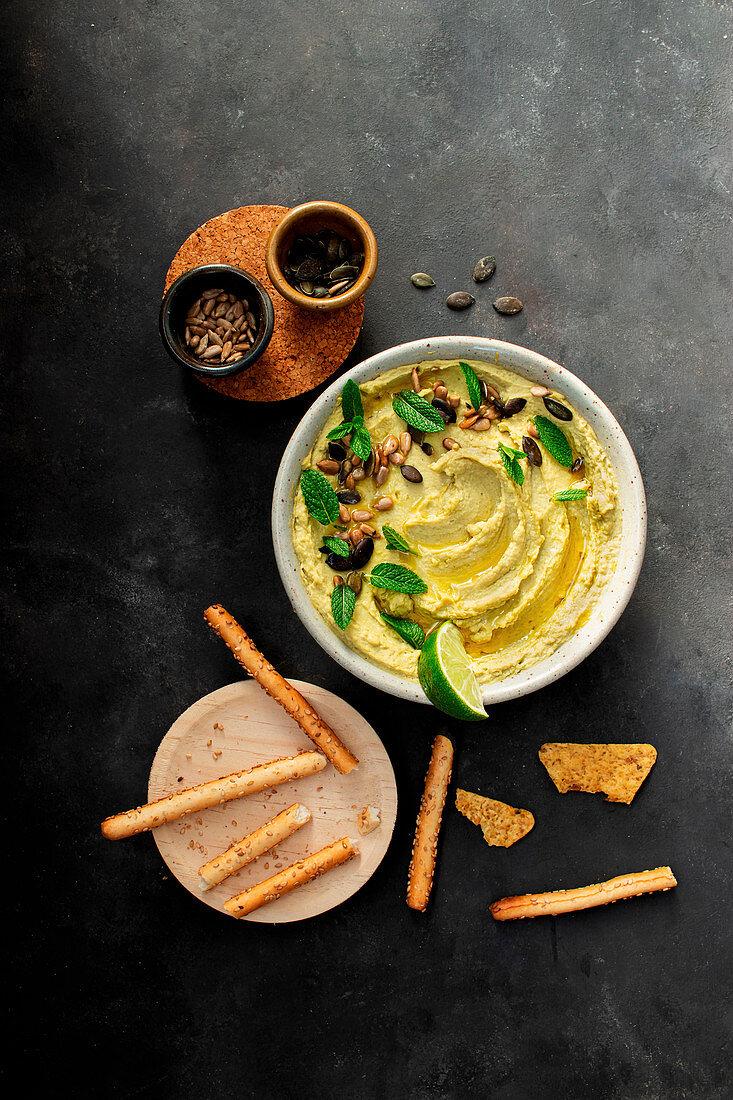 Hummus peas in bowl near crackers
