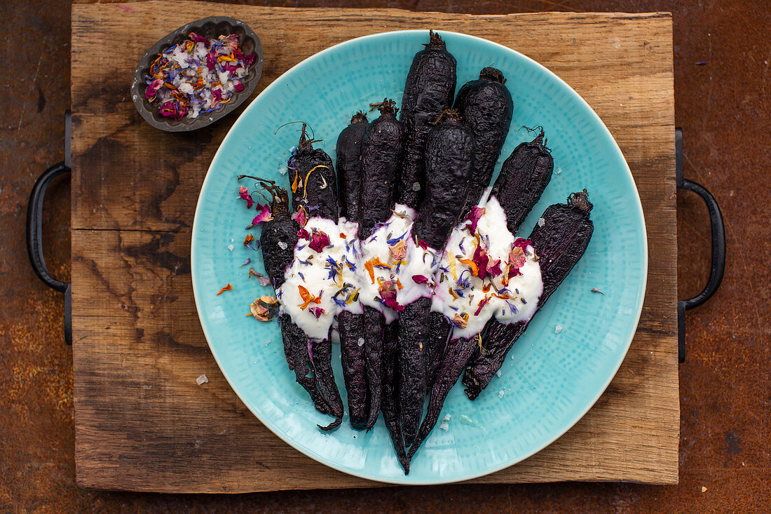Roasted purple carrots with a yogurt dressing topped with seasal
