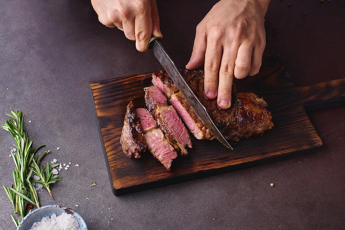 Male hands cutting cooked until medium ribeye steak on wooden cutting board