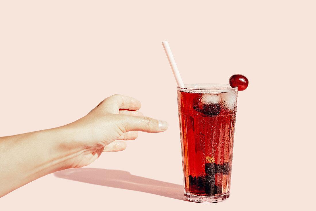 Hand greift nach Glas Traubensaft mit Eiswürfeln