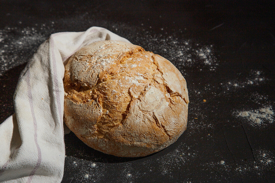 Fresh bread with crunchy crust placed on linen cloth on table against black background