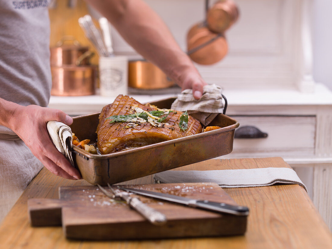 Grilled crispy roast pork being removed from the oven