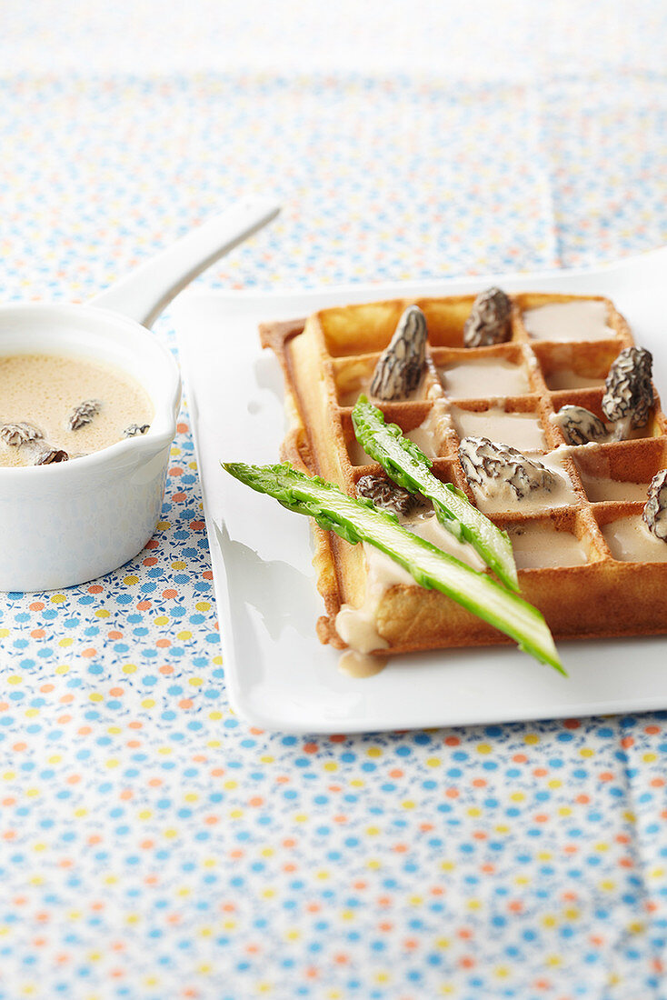 A waffle with green asparagus and morel mushroom cream