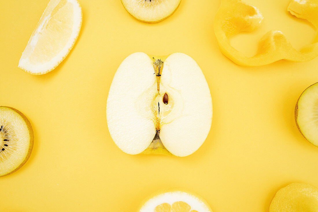 Various fresh fruits and vegetables arranged on yellow background