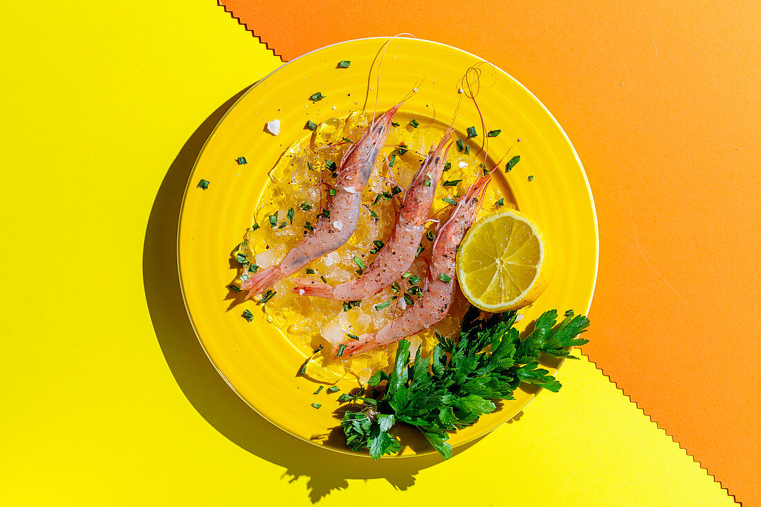 Tasty prawns on yellow plate with half of lemon and bunch of fresh parsley on multicolored background