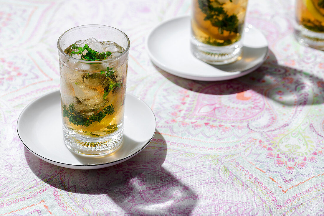Glasses of cold refreshing tea with ice cubes and lemon slices placed on table