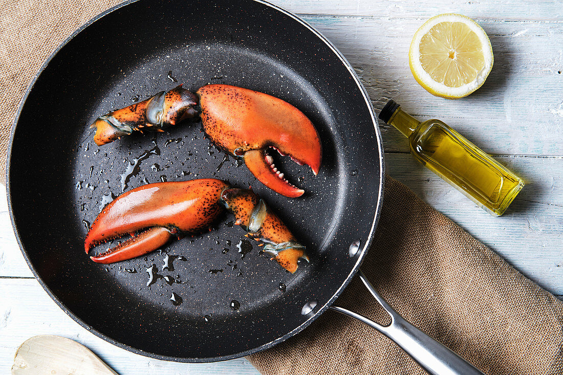Lobster claws in pan, bottle of olive oil and half of juicy lemon