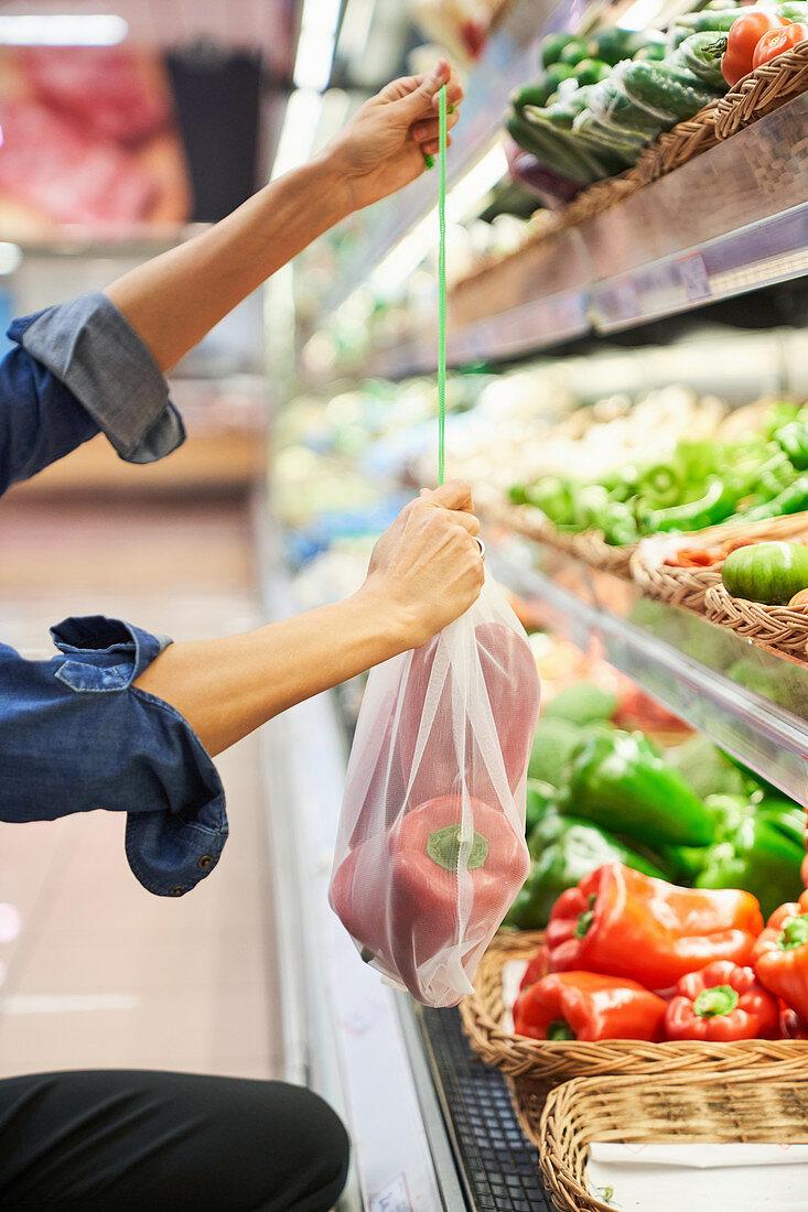 Frau im Supermarkt gibt Paprikaschoten in recycelbaren Beutel