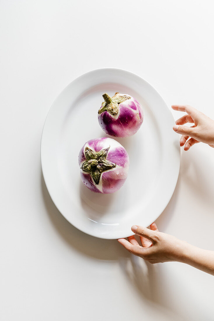 Fresh eggplants on plate on white table