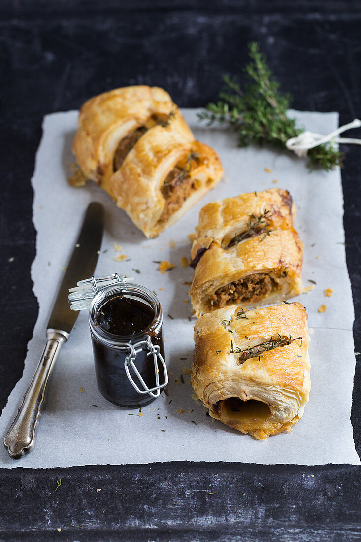 Sausage puffs with golden surface and tender texture, jar of dark pasty sauce and fresh thyme sprigs