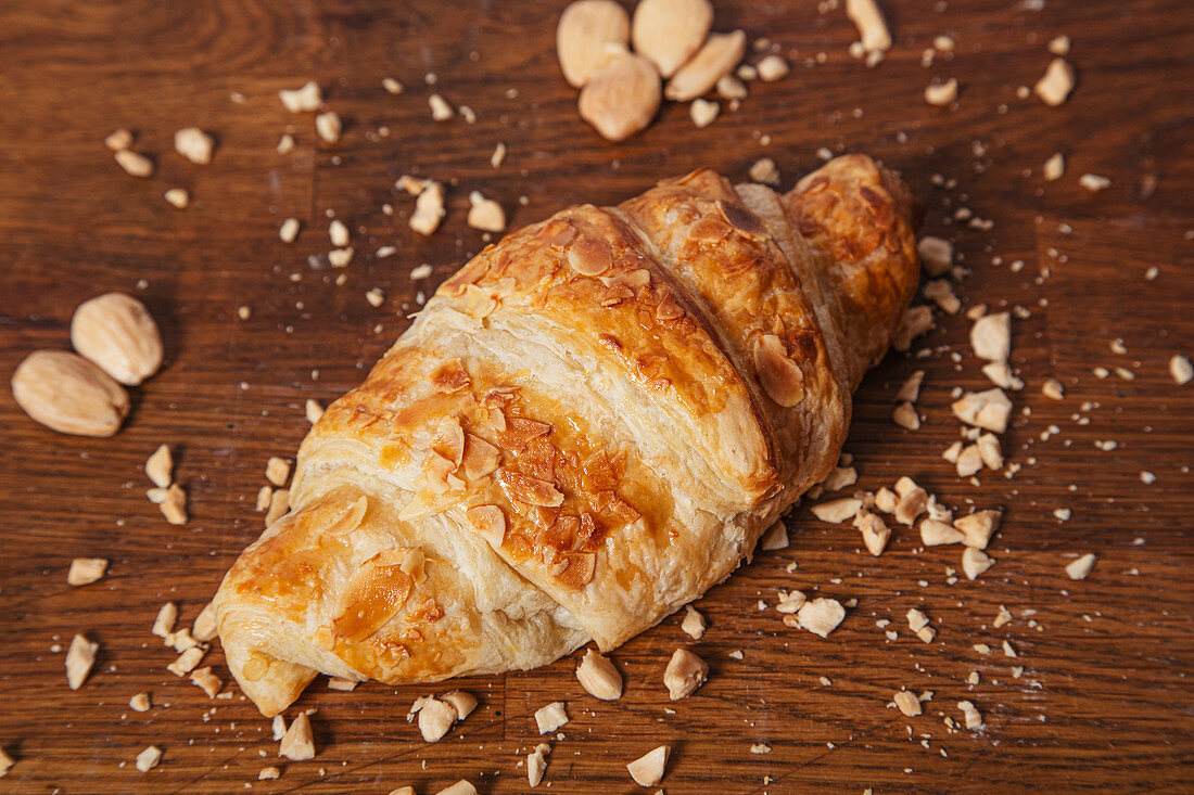 Croissant with golden crust on wooden table with crumbs of almond nuts